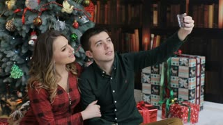 Happy couple taking selfies on smartphone , siting near Christmas tree.