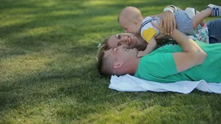 Happy family have fun lying on the grass. Little baby have fun with his parents