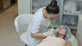 High angle view of woman lying on the couch in cosmetic cabinet while beautician in medical gloves doing skin treatment with ultrasonic machine