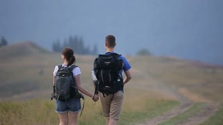Hikers man and woman lovers trekking walking with backpacks in trail at mountains.Couple holding hands hiking outdoors at mountains.