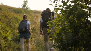 Hikers man and woman lovers trekking walking with backpacks in trail at mountains.Couple holding hands hiking outdoors at mountains