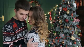 Husband with his wife celebrate Christmas and New Year. Husband and wife near New year tree. Husband embraces his wife. Slow motion.