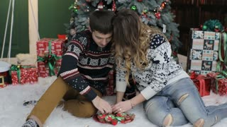 Husband with his wife celebrate Christmas and New Year. Husband and wife near the  New year tree. Husband embraces his wife.