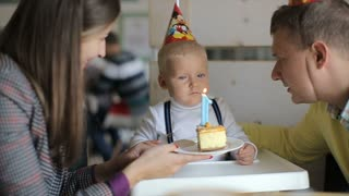 Little boy blows out candles on birthday cake at party