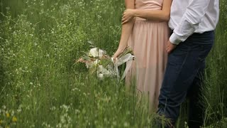 Loving couple standing in the grass.girl with a bouquet of flowers