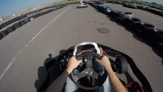 Man drives go kart on track very fast, filmed from the driver's view, man holds the steering wheel with his hands