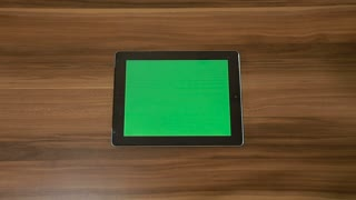 Man Hand Using Horizontal Digital Tablet with Green Swipe Right on the Background of Wooden Table.