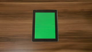 Man Hand Using Vertical Digital Tablet with Green swipe Down on the Background of Wooden Table