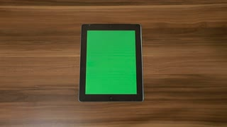Man Hand Using Vertical Digital Tablet with Green swipe left on the Background of Wooden Table