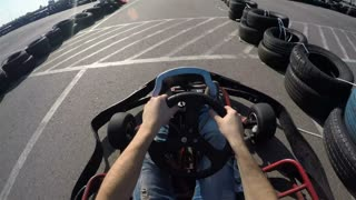 man holds the steering wheel with his hands, Man drives go kart on track, Karting filmed from the driver's view