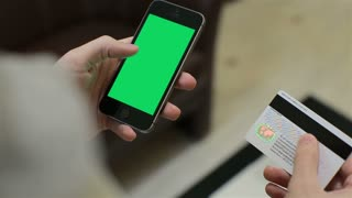 Man inserting credit card number on mobile phone, online banking