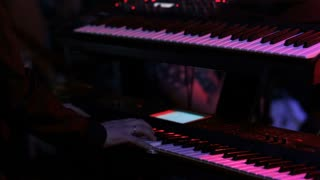 Man playing on synthesizer at a rock concert