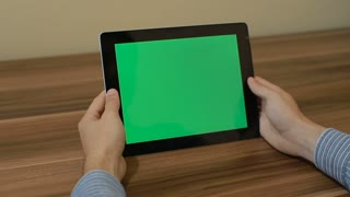 Man Using Horizontal Digital Tablet swipe left hand gestures with Green Screen on the Background of Wooden Table.