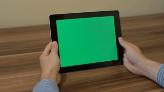 Man Using Horizontal Digital Tablet swipe up hand gestures with Green Screen on the Background of Wooden Table.