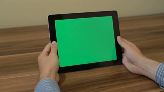 Man Using Horizontal Digital Tablet tap hand gestures with Green Screen on the Background of Wooden Table.