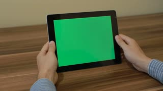 Man Using Horizontal Digital Tablet zoom in hand gestures with Green Screen on the Background of Wooden Table.