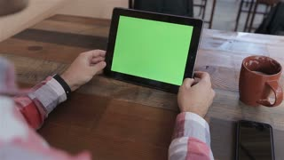 Man Using Tablet PC in Landscape Mode at Home.Tablet with Green Screen.Causal Lifestyle.