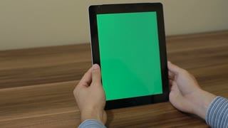 Man Using Vertical Digital Tablet swipe down hand gestures with Green Screen on the Background of Wooden Table