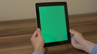 Man Using Vertical Digital Tablet swipe left hand gestures with Green Screen on the Background of Wooden Table