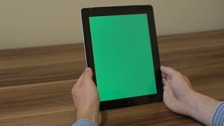 Man Using Vertical Digital Tablet tap hand gestures with Green Screen on the Background of Wooden Table.