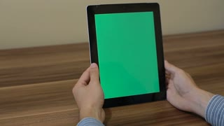 Man Using Vertical Digital Tablet Zoom out hand gestures with Green Screen on the Background of Wooden Table