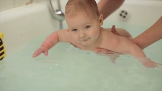 Mother bathes the baby in the bath.child swims in the bath