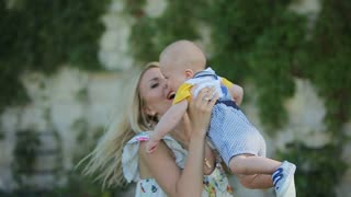 Mother playing with young son in the backyard. Baby have fun