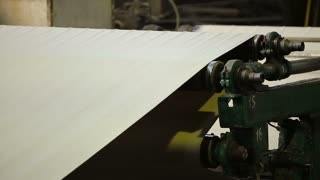 paper rolling through an automated paper bag making and folding assembly machine