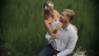 Pretty woman embraces with handsome young man on the grass