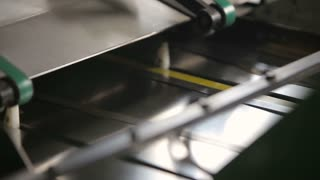 Production line at a print factory, feeding paper, close up