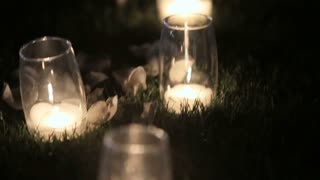 Romantic burning white candles in glass vases standing on a grass for an evening wedding ceremony.