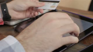 Shopping on-line with credit card on digital tablet.close up