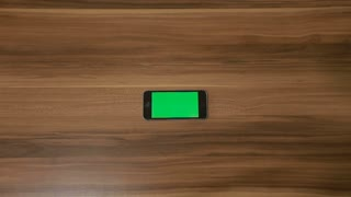 Smartphone Double tap hand gesture on the Background of Wooden Table.Horizontal