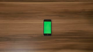 Smartphone Double tap hand gesture on the Background of Wooden Table.Vertical