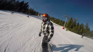Snowboarder riding and falling on ski slope in sunny ski resort
