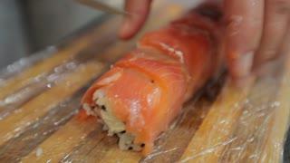 Sushi chef cutting sushi rolls