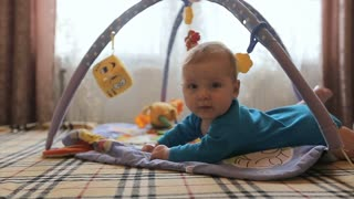 The baby lies on a bed and having fun