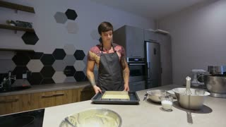 The young man put the cake in the oven for baking. A man prepares a cake for the modern kitchen