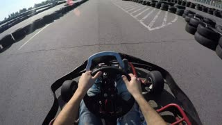 tree drivers drive go kart, Karting filmed from the driver's view, Man holds the steering wheel with his hands, Man drives go kart on track
