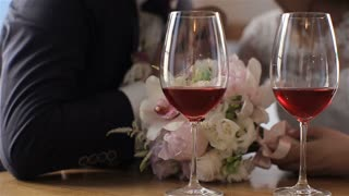 Two glasses of red wine on a background of beautiful wedding couple. Slow motion