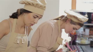 two young women are making macaron