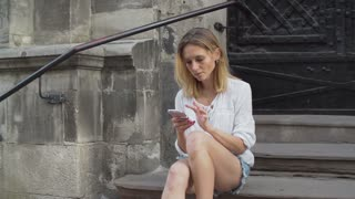 A beautiful girl in shorts is using the app on her smartphone