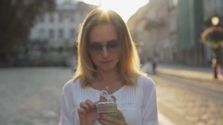 A beautiful girl in sunglasses uses an app on her smartphone
