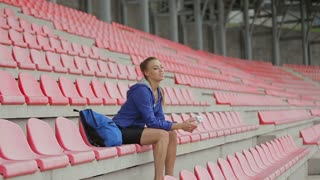 A beautiful woman drink water after running and training at the stadium's chairs