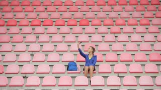 A beautiful woman makes a selfie after running and training at the stadium's chairs