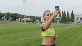 A beautiful woman makes a selfie before running at the stadium