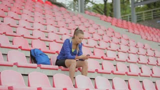 A beautiful woman using a smartphone after running and training at the stadium's chairs