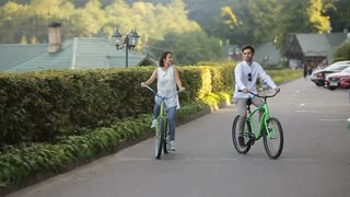 A couple rides on bikes and smiles.Young couple having fun on weekends.