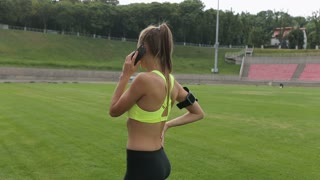 A sports girl speaks on the phone before the jog at the sports stadium