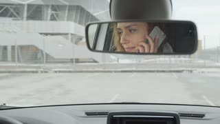 A young woman talking on the phone in the car